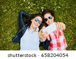 two happy women laying on grass ... | Shutterstock . vector #658204054