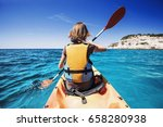 young woman kayaking in the sea.... | Shutterstock . vector #658280938
