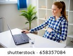 pregnant woman working in office | Shutterstock . vector #658357084