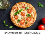 pizza margherita on black stone ... | Shutterstock . vector #658408219