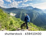 male hiker on a mountain summit ... | Shutterstock . vector #658410430