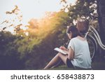 Stock photo beautiful woman writing into her diary in the park 658438873