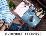 open suitcase with casual... | Shutterstock . vector #658564924