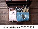 open suitcase with casual... | Shutterstock . vector #658565194