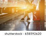 Small photo of Beautiful young woman sitting in the train station waiting a train with Red Luggage and Baggage on a Platform Trolley while open map for finding place in the morning,vintage color,selective focus