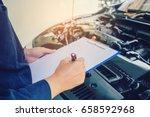 mechanic holding a clipboard of ... | Shutterstock . vector #658592968