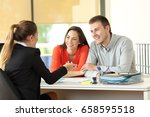 Small photo of Happy couple being attended by office worker at office