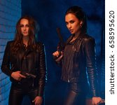Two sexy woman in black leather clothes with guns. Girls with weapon at night street. Dark street, orange light, blue fog