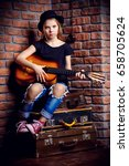 Small photo of Modern child girl playing guitar and singing a song. Rock star, rock music, pop music concept.
