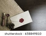 Small photo of letter seal with wax seal stamp on the wood table and fabric , Pine cone on the fabric