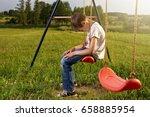 sad lonely boy sitting on swing ... | Shutterstock . vector #658885954