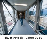 Small photo of Man boarding in airport gate or jet bridge or jetway or airbridge to a plane, tunel vision, perspective