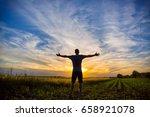 man standing in an open field... | Shutterstock . vector #658921078