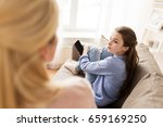 Small photo of people, conflict and family concept - sad girl with smartphone looking at her mother at home