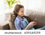 children, technology and communication concept - smiling girl texting on smartphone at home - stock photo