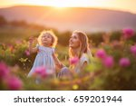 Stock photo beautiful couple mother and cute little daughter are walking in blossom roses garden over yellow 659201944