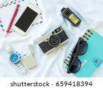 Small photo of Flat Lay photo with props are Air letter, watch, pen, Flash, Camera, Glasses, Charger, Blue Notebook and smartphone on white fabric background.