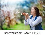 a woman makes a wish  blowing... | Shutterstock . vector #659444128