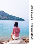 Small photo of A woman is sitting at ease by the sea .Young girl enjoying blue mediterranean view alone Travel Lifestyle concept adventure vacations outdoor. Melancholy solitude emotions