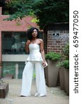 Small photo of black African American Lady in elegant white outfit posing in the street