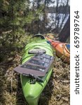 Small photo of Portable solar panels lie on a green kayak in the forest and accumulate energy.
