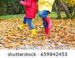 Small photo of Two little children playing in red and yellow rubber boots in autumn park in colorful rain coats and clothes. Closeup of happy kids dancing and walking through fall autumnal golden leaves and foliage.
