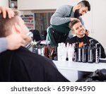 Small photo of Young positive male hairdresser accurately cutting beard of client at hair salon