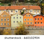 Small photo of Four colorful three-story houses abut up against each other in a row along a walkway and overlooking the Danube River in Passau, or Lower Bavaria in Germany