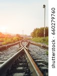 Small photo of Two railways tracks merge close up.Vintage tone. Vertical photography.
