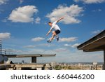 Small photo of A man is jumping from roof to roof. Parkour. Active lifestyle. Courage. Adrenalin. Roofer