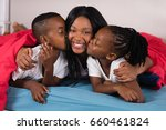 siblings kissing their mother... | Shutterstock . vector #660461824