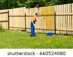 workman paints wooden fence...   Shutterstock . vector #660524080