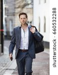 Small photo of Businessman is walking to work through the city. He is carrying a holdall bag and his smart phone.