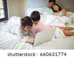 sibling using laptop in bedroom ... | Shutterstock . vector #660631774