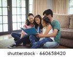 family watching photo album... | Shutterstock . vector #660658420