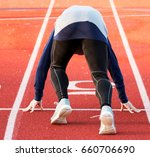 Small photo of A sprinter training for the 100 mete dash on a high school track in the winter