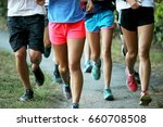 Small photo of A cross country team runs a workout in a group in a park outside.