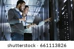 Small photo of Male IT Specialist Holds Laptop and Discusses Work with Female Server Technician. They're Standing in Data Center, Rack Server Cabinet is Open.
