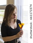 Small photo of Medium shot of beautiful young woman in black top staring at cocktail in amber glass, with window in the background