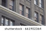 Small photo of Establishing shot of generic brick facade building day DX photo. Tight tilt up office apartment windows in city