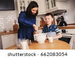 kid boy helps mother to cook in ... | Shutterstock . vector #662083054