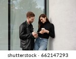 Stock photo outdoor shot of young attractive woman flirting with man she gives number phone with shy smile 662147293