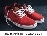 Small photo of Pair of stylish red sneakers on dark background
