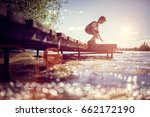 boy playing on a pier by lake... | Shutterstock . vector #662172190