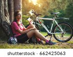 woman cyclist resting under a... | Shutterstock . vector #662425063