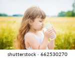 the child holds a glass of... | Shutterstock . vector #662530270