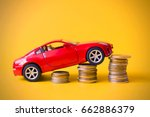 red toy car rides up a pile of... | Shutterstock . vector #662886379