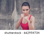 Small photo of Woman power, self defence concept. Close up portrait of attractive serious fit boxer, ready for fight, on concrete wall background, wearing pink fashionable sport wear