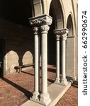 Small photo of Medieval colonnade from the 12th century BCE. Late afternoon with long shadows. Cloister of a medieval church, warm sunlight and long shadows.