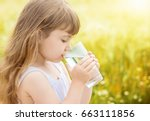 the child holds a glass of... | Shutterstock . vector #663111856